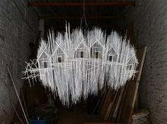 Working with hundreds of steel rods and pieces of piano wire, Spanish artist David Moreno constructs unwieldy sculptures that look like 2D sketches. Usually centered around a structure or row of house-like buildings, each artwork is designed to look like a haphazard collection of sticks, perhaps som
