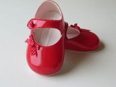 Striking baby girl red patent Baypod shoes by Early Day The shoes are finished of with a red and white polka dot ribbon bow and fasten with a strap