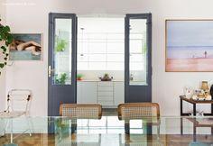 Sala de jantar com porta pintada de cinza e corredor que dá para a cozinha ao fundo.