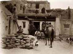 A grand photo of an Indian Village. It was made in 1905 by Edward S. Curtis. The illustration documents Hopi adults gathered outside a doorway, with children on the roof, and dogs and horse in foreground.