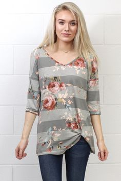 Get twisted detail top on left hip with a cute floral pattern over tonal stripes. Darker stripes are grey in color with the lighter ones being a heathered grey. Three quarter length sleeves. Very soft material with stretch.