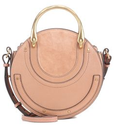 Chloé - Pixie leather and suede shoulder bag - Chloé's Pixie bag is the season's statement accessory, featuring a glossy golden top handle for a jewellery-inspired look. Crafted in Italy from beige-hued leather and suede, this style comes in a disc-inspired design and is roomy enough to fit your essentials. Carry this piece over your shoulder, crossbody or in hand. seen @ www.mytheresa.com