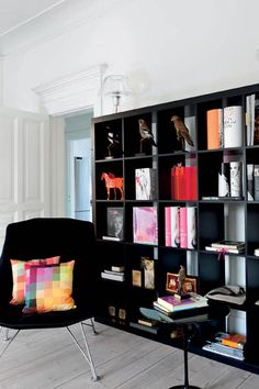 Artistic storage in black, color coordinated with chair and pillows.