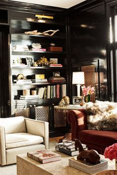 Styled bookshelves in a black-painted library lounge with decorative grille cover.