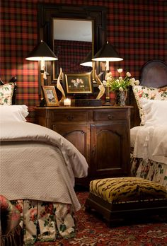 An English Gentleman's guest bedroom features wool tartan plaid upholstered walls, antique French iron headboards and an antique oriental rug.