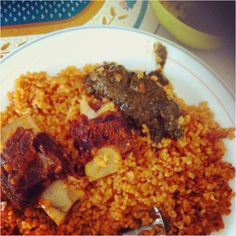 """Famous west African dish! """"Jollof Rice"""" Spicy rice with beef meat and spicy, peppery greens on side called """"bissap"""" Gambians love spicy things. One of my fav Gambian dishes!"""