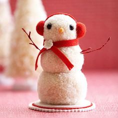 It must be snowing pom-poms -- this frosty figure is made from a stack of three. Stack three pom-poms for a snowman shape. Add a needle-felted nose, earmuffs, a felt scarf, and glittery arms for personality.