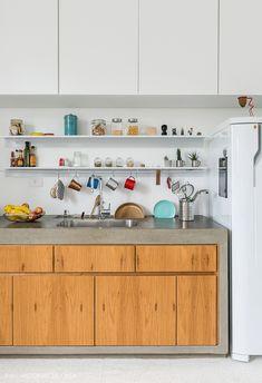 Cozinha integrada tem bancada de concreto com armários de madeira.