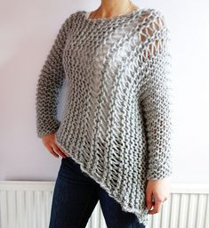 This unique and stylish bulky asymmetrical sweater hanging loose on a side is knitted on super-sized needles.
