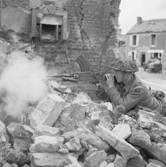 A Bren-gunner, Private W Wheatley of 'A' Company, 6th Battalion, Durham Light Infantry, 50 Division, giving supporting fire from a ruined house in Douet, near Bayeux, Normandy.