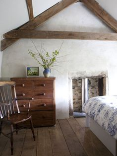 Country farmhouse bedroom with exposed wooden beams