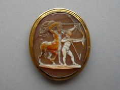 Sardonyx cameo, 16th C. The centaur Chiron teaching Achilles to draw the bow; he holds an arrow in each hand and his mantle flies out behind him. Length: 1 inches (in gilt mount). Purchased from: Alessandro Castellani, 1872. -British Museum-