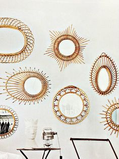 Rattan mirror gallery wall- get the look. These are cool wall art, I'd like them without the mirror part.