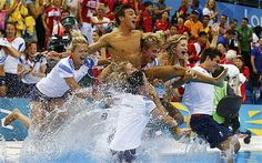 Tom Daley being thrown into the pool in celebration by his team-mates after winning the bronze medal.
