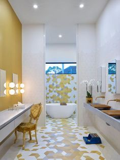 This modern kids bathroom was designed for three girls, and it has three sinks, three makeup stations and fun, colorful geometric tiles.