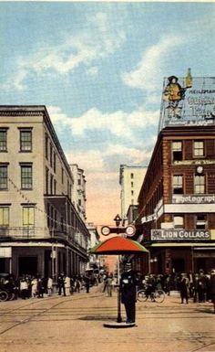 Postcard view 1910s, Canal Street looking down Royal Street in to the French Quarter. Traffic officer operates hand rotated stop/go sign with shade umbrella at intersection. Multiple streetcar line tracks visible.