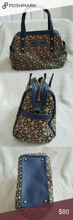 """DKNY Handbag NWOT! Adorable small handbag from DKNY. Brown and tan logo pattern with Navy blue accents and gold hardware. Inside is cream colored lining with the same logo pattern. Features two outside pockets, zippered main pocket with two open pockets and one zippered pocket on the inside. Measures 11"""" wide by 8"""" high. DKNY Bags"""