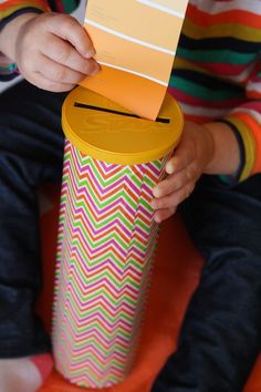 toddler dropping paint swatches into pringles can for fine motor activity
