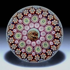 And another fabulous concentric cane paperweight made by Michael Hunter for Twists Glass in 2016. In the centre of the paperweight is an owl picture cane that is surrounded by 4 concentric rings of complex murrine canes with small spacer canes between the 2nd and 3rd circle. The 1st ring comprises 11 pink murrine canes with tiny hearts, the 2nd ring comprises 11 pink yellow and green murrines with stars, the 3rd ring comprises 22 orange