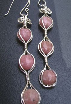 Rhodonite Earrings by shazzabeth, via Flickr I'm not sure but I don't think these have been strung through a wire.  They look caged.  Beautiful.
