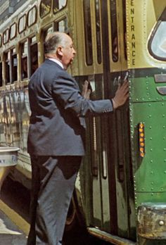 """ALFRED HITCHCOCK  CAMEO : he misses the bus in """"NORTH BY NORTHWEST"""" (1959)."""