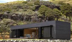 Off-Grid Storm Cottage is a Solar-Powered Timber Box on New Zealand's Great Barrier Island - Located on the eastern side of New Zealand's Great Barrier Island, the self-sustaining Storm Cottage operates entirely off-the-grid. Powered by the sun and protected by it with a series of operable metal screens, the north-facing home stays cool in summer and warm in winter.