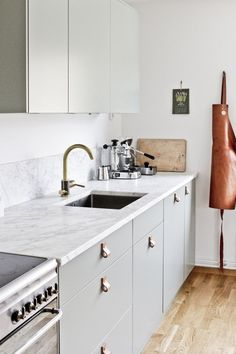 our kitchen - green fronts, marble counter top, smeg stove, brass tap from tapwell and leather handles