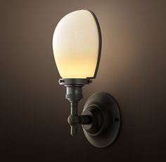 RH's Vintage English Oval Sconce:Recalling the light-focusing designs of early task lights, our sconce combines the update of a glass shade with the vintage details of a metal rim, thumbscrews and other factory-worthy accents.