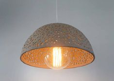 This ceramic lamp shade is hand made of stoneware. I use a technique of knitting the clay which creates holes allowing the light to