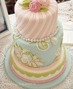 tiered cake ... gorgeous pastels ... pink, blue green ... different patterns for each layer ... luv the wide stripes of pink and white swirled up to the rose bouquet ...