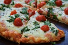 Cheese pizza with tomatoes and fresh basil.
