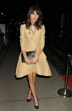 """Alexa Chung in Carven """"Cotton Faille Jacket"""" and poplin skirt with black heels and black clutch."""