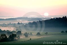 Sunset over misty landscape in Czech republic with yellow and pink sky