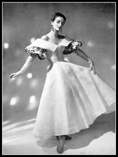 Model in lovely white organdy dress, puffed sleeves are embroidered with red roses and green leaves, by Grès, photo by Georges Saad, 1954
