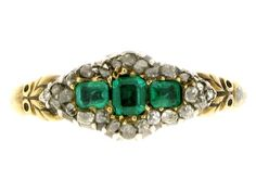Georgian emerald and diamond ring, c. 1820. Three octagonal emeralds to centre, outer stones set in opposite orientations to the centre, approximate total weight is 0.40ct. Outer border is comprised of twenty-six rose cut diamonds in a silver cut down setting, with an approximate weight of 0.26ct. Mounted and set in silver and gold, to carved shoulders.