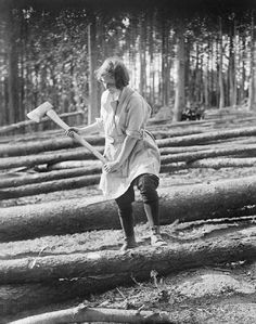WOMEN AT WORK DURING THE FIRST WORLD WAR© IWM (Q 30695)  A member of the Women's Forestry Corps uses an axe to mark felled tree trunks for sawing during the First World War.
