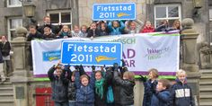 """Best Cycle City of the Netherlands 2014 competitors: School children with the award on the steps of city hall: signs with the title """"Cycling City 2011"""""""