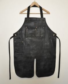 "Split-Leg Waxed Apron. This is a classic style apron with a wax coating. It also features approximately a 12"" split from the bottom centre of the apron allowing the wearer to to sit with their legs apart."