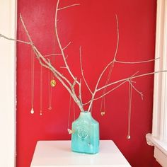 Super easy, and super pretty. Put some branches in a funky old vase and hang your necklaces, as done here.