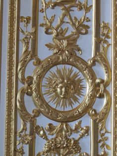 Versailles, France - Versailles Palace, Detail of the wainscotting with the emblem of the sun representing the power of the king and the royal scepter and the hand of justice