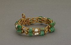 Gold bracelet set with emeralds and pearls strung on gold wire.
