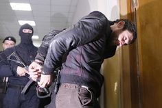 "Scapegoat or killer? ""Zaur Dadayev, [one of two Chechens] charged with involvement in the murder of Russian opposition figure Boris Nemtsov, is escorted inside a court building in Moscow [today] March 8, 2015.  REUTERS-Maxim Shemetov"""