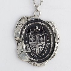Five Fleur de Lys Talisman Necklace    This handcrafted wax seal necklace features five fleur de lys which are symbolic of light and life. In Latin, it reads Virtue Is Its Own Reward.