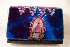 Unusual and beautiful evening clutch. The scene is a grape arbor made of hand dyed lace that has been bead embroidered. Under the arbor is a working fairy door (It actually opens). Surrounding the door is hand dyed silk with more bead embroidery. The background is hand dyed rayon velvet. All attached to a clutch blank in black with a cord strap.  The purse measure 8x5. It will fit a large cell phone.