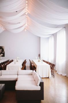 Ceiling drapes + fairy lights! Loving the white theme.