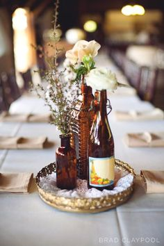 bottle centerpieces {credit: Floral Designs by Christa Rose}- this is where vanity mirrors come in handy- or your frames =)
