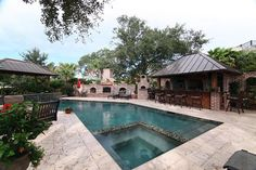 Geometric swimming pool located on James Island. The entire outdoor space encompasses a swimming pool with spa, an outdoor bar and kitchen, fireplace, brick pizza oven overlooking sweeping views of the Lowcountry marsh.