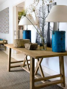 Modern farmhouse decor: A rustic wood table in a living room styled with Two blue tin lamps, a black and white photograph, flowers in a glass jar, and carved wood bowls.