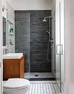 Dans une salle de bain étroite, le carrelage gris anthracite sur le mur du fond donne de la profondeur à la douche italienne