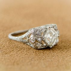 One of the most unique Antique Engagement Rings I've ever seen. A stunning Asscher Cut surrounded by a beautiful handmade platinum setting. Circa 1930.